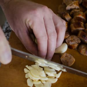 Close up shot of Alex chopping garlic. Jambalaya Recipe from garlicdelight.com.