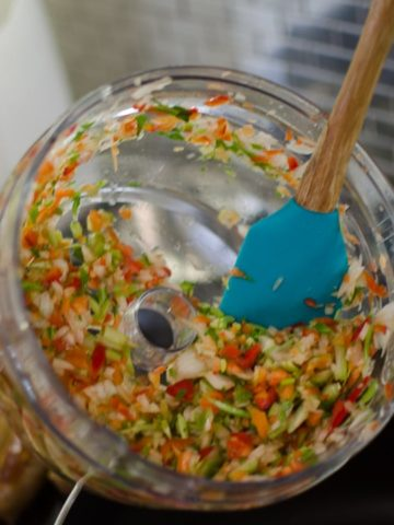 Close up shot of pouring holy trinity into pot. Jambalaya Recipe from garlicdelight.com.