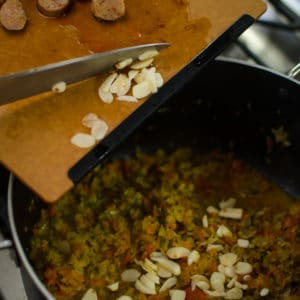 Shot of adding garlic to the pot. Jambalaya Recipe from garlicdelight.com.