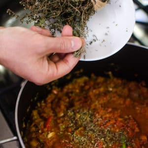 Shot of adding dried thyme to the pot. Jambalaya Recipe from garlicdelight.com.