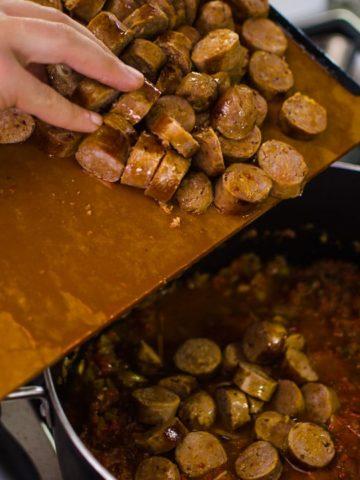 Shot of adding chopped sausage to the pot. Jambalaya Recipe from garlicdelight.com.