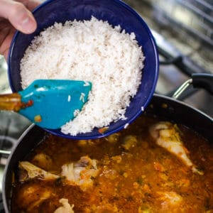 Shot of adding rice to the pot. Jambalaya Recipe from garlicdelight.com.