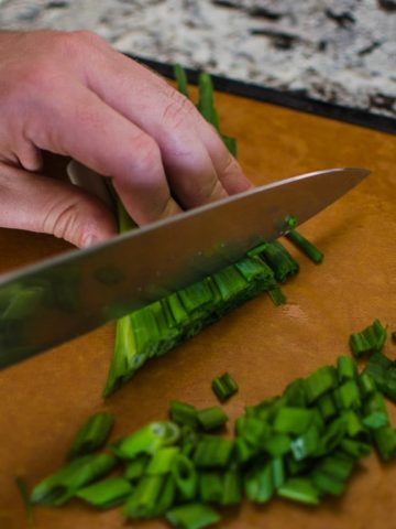 Close up shot of Alex chopping green onions. Jambalaya Recipe from garlicdelight.com.