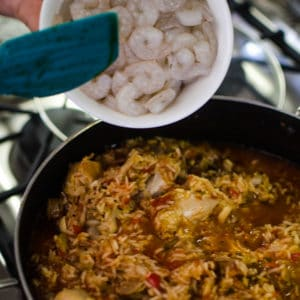 Close up shot of adding shrimp to cooked Jambalaya. Recipe from garlicdelight.com.