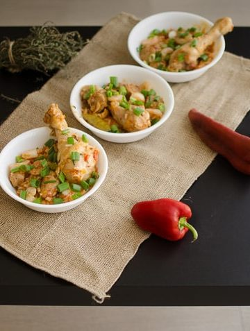 Long shot of cooked Jambalaya in bowls on black table. Recipe from garlicdelight.com.