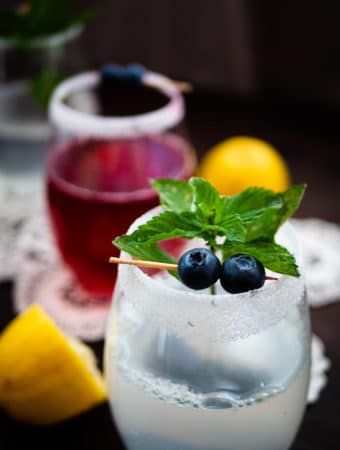 Lemonade infusions with mint and blueberry garnishes plus lemon wedges.