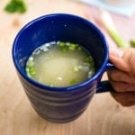 A blue mug with miso soup and green onions for the 5-Minute Homemade Vegan Miso Soup recipe