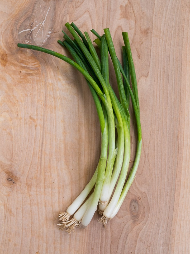 A bunch of green onions on a wooden background