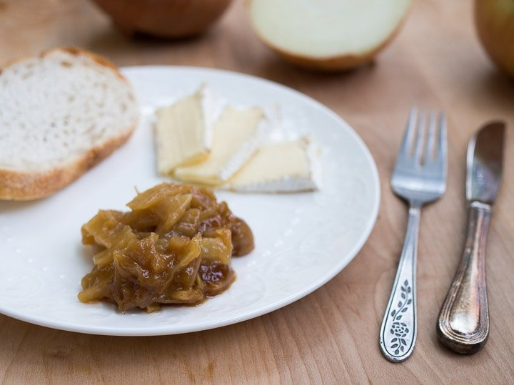 A view of caramelized onions next to brie and sliced bread