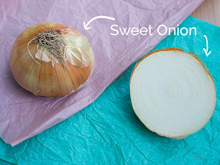 A view of a sweet onion chopped in half to see the cross sectional view and the outer skin