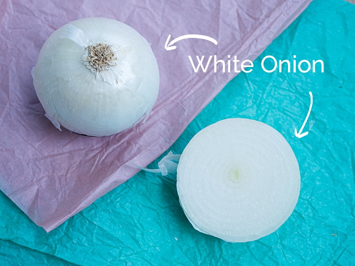 A view of a white onion chopped in half to see the cross sectional view and the outer skin
