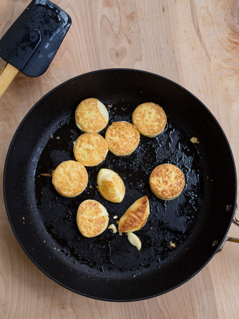 A view of the fry pan with golden brown egg tofu slices for the pan-fried egg tofu with cilantro recipe