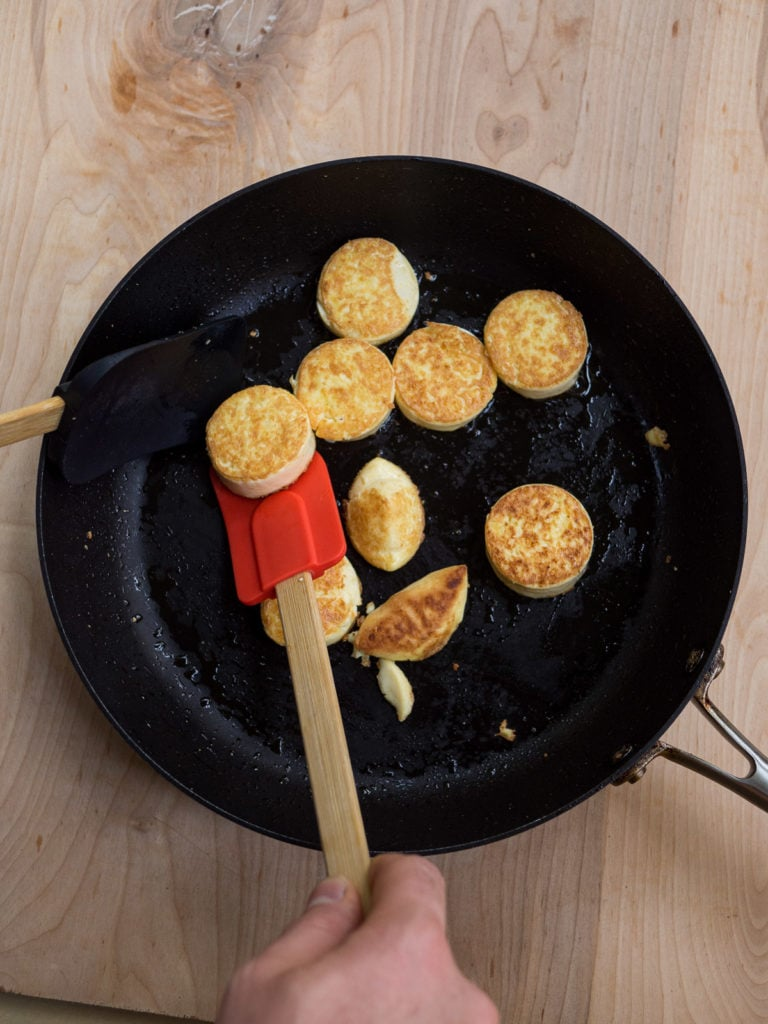 A view of the fry pan with two spatulas for flipping the golden brown egg tofu slices for the pan-fried egg tofu with cilantro recipe