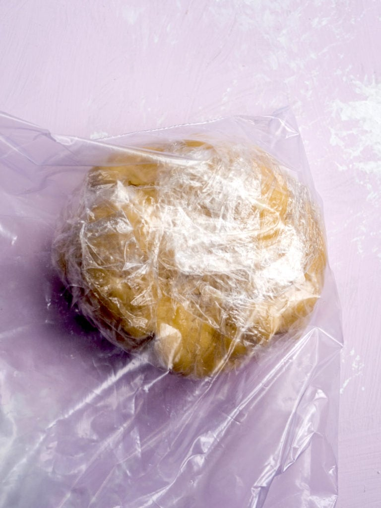 A ball of pâte brisée dough wrapped in plastic wrap and in a zip loc bag
