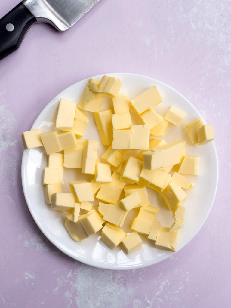 Frozen butter cut into small cubes on white plate