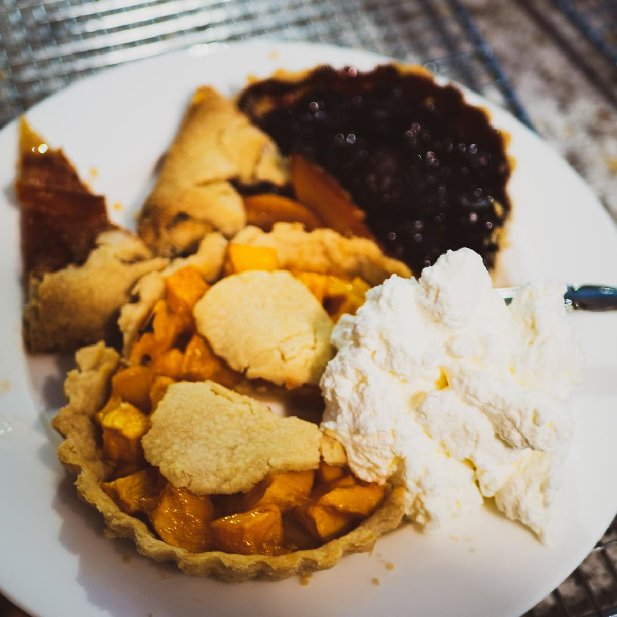Different fruit pies on white plate with whipped cream