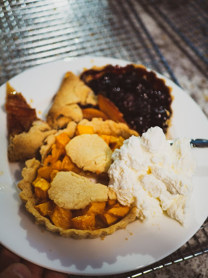Cherry pie, mango pie, and 2 slices of peach galette with a generous amount of whipped cream
