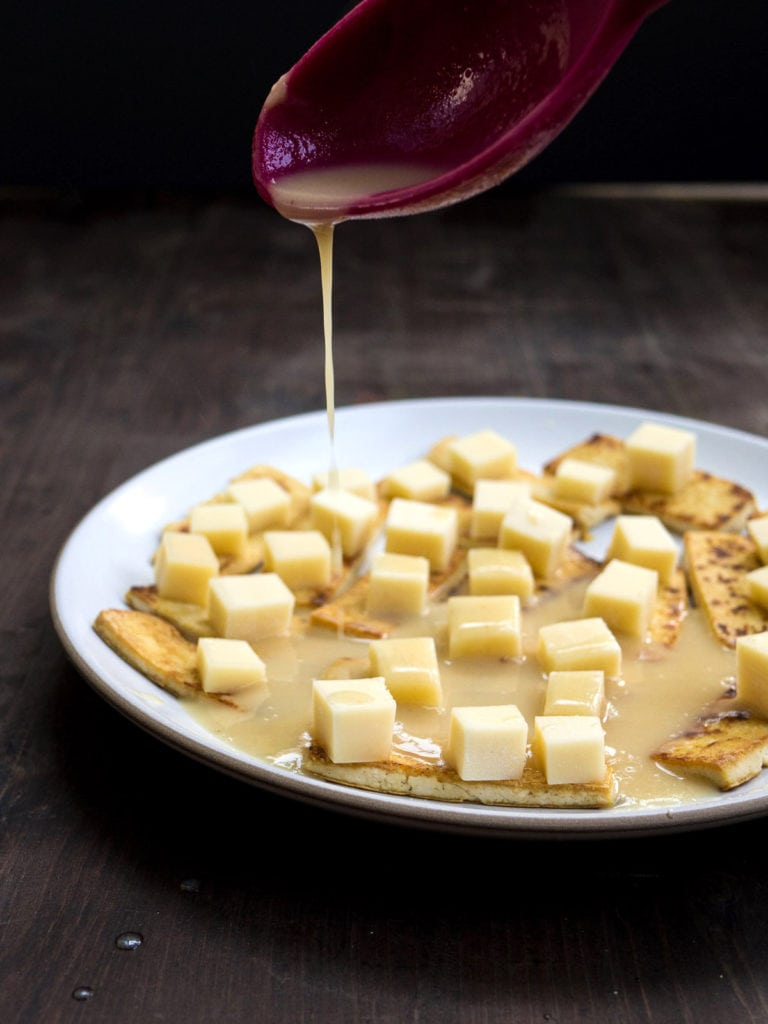 A spoon pouring gravy over the tofu and cheese cubes