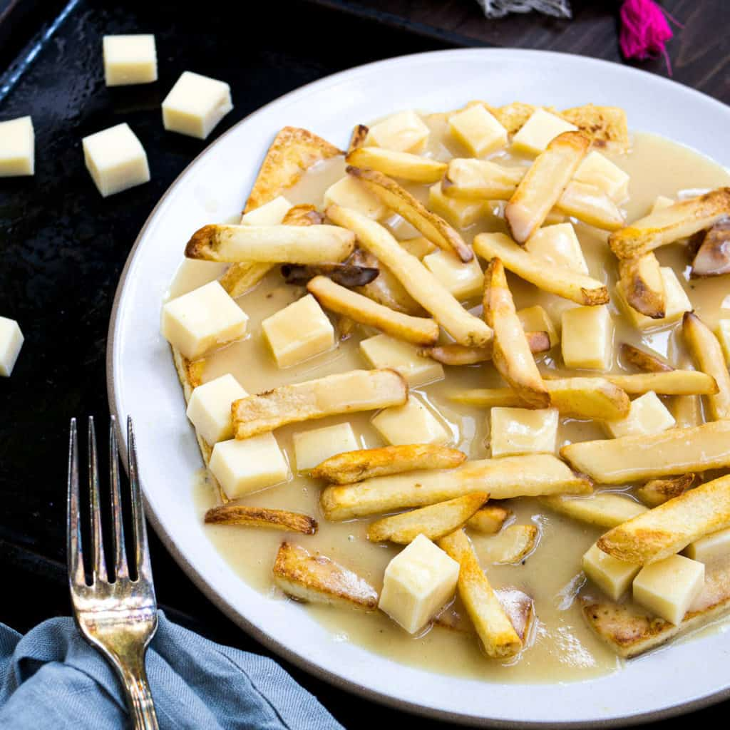 Poutine with tofu and fries on a white plate