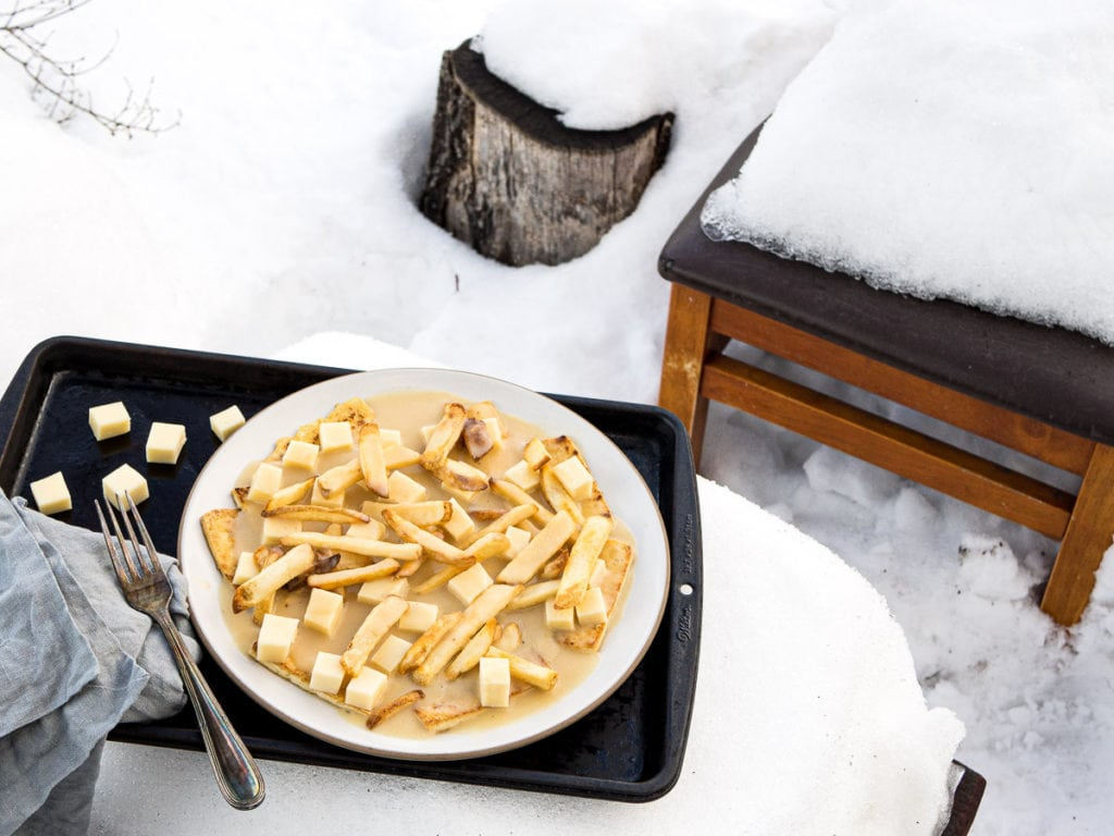 A tray with a plate of poutine with tofu and fries on a table packed with snow
