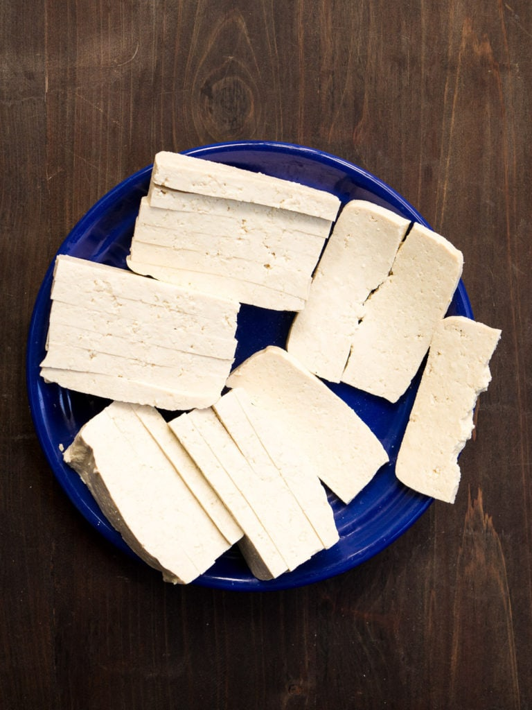 Thinly sliced super-firm tofu on a blue plate