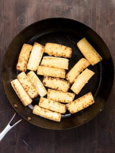 Pan-fried slices of super-firm tofu in a frying pan
