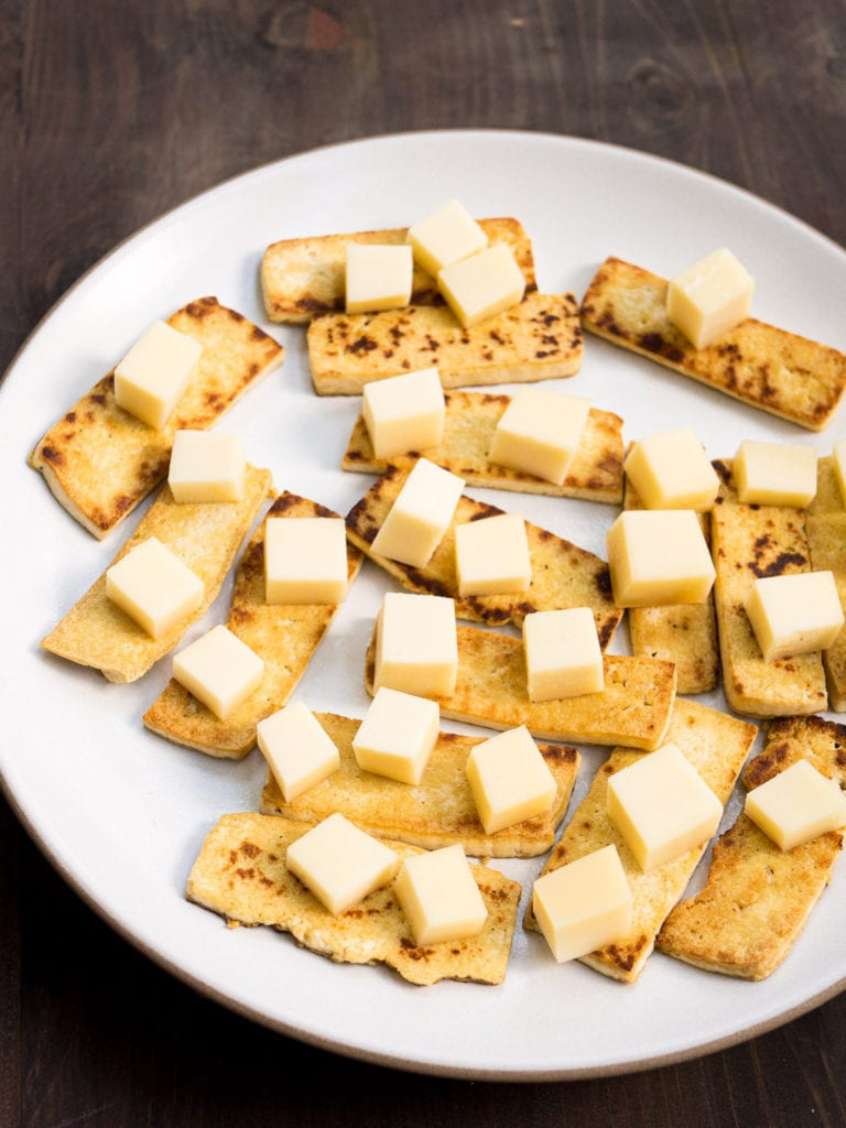 Cubes of cheese on top of slices of tofu