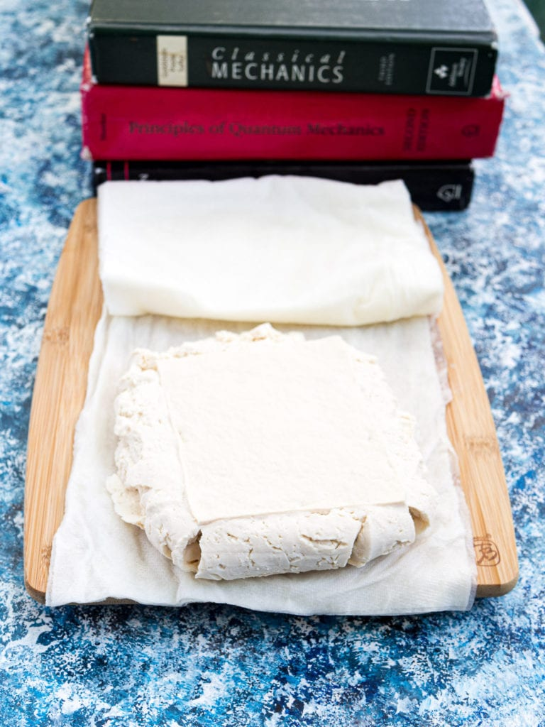 Pressed tofu with paper towels underneath on top of a chopping board and a stack of books nearby