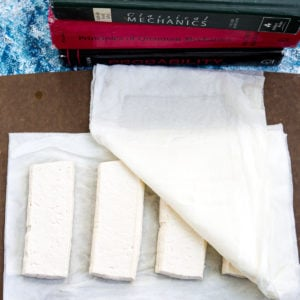 Pressed tofu with paper towels underneath and on top next to a stack of books