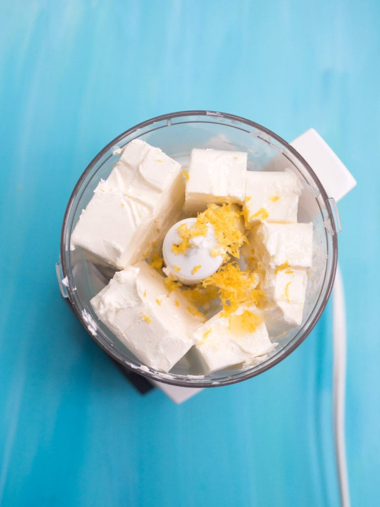 Blocks of cream cheese in a blender with lemon zest