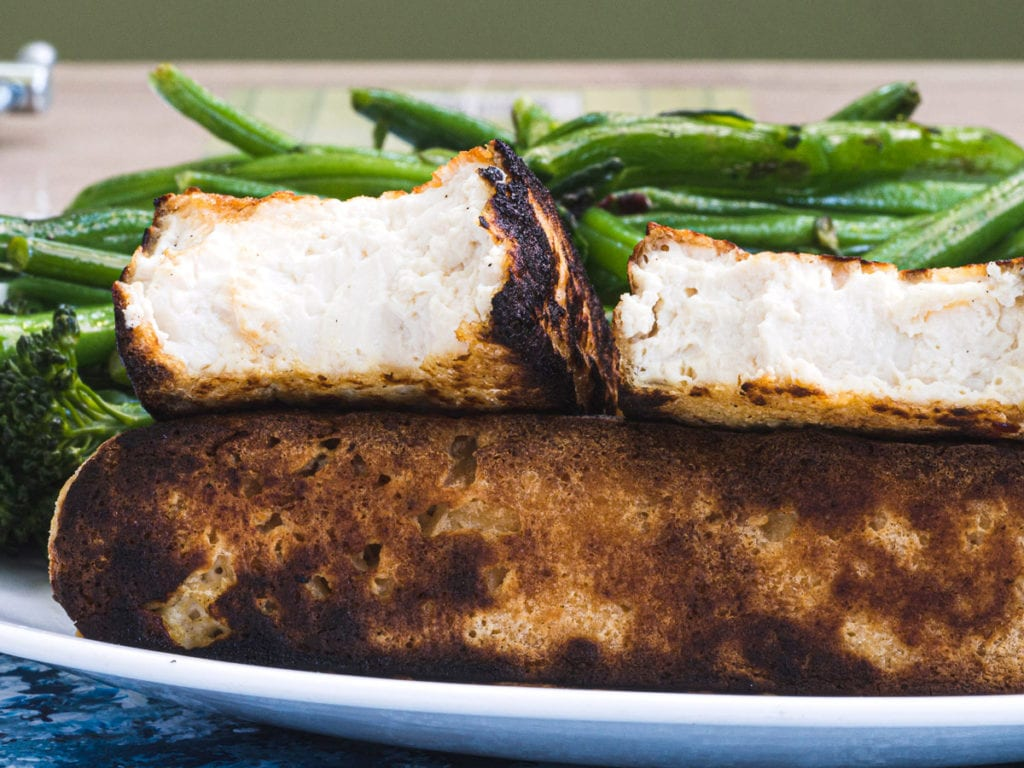The inside of fried pressed tofu served with green beans