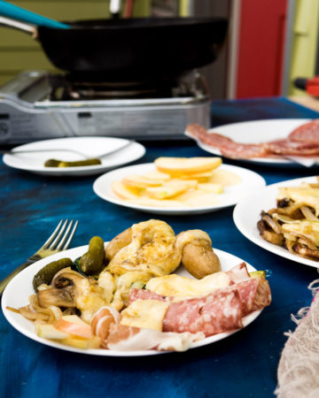 A table set up for making a raclette dinner, including a hot pot-style stove