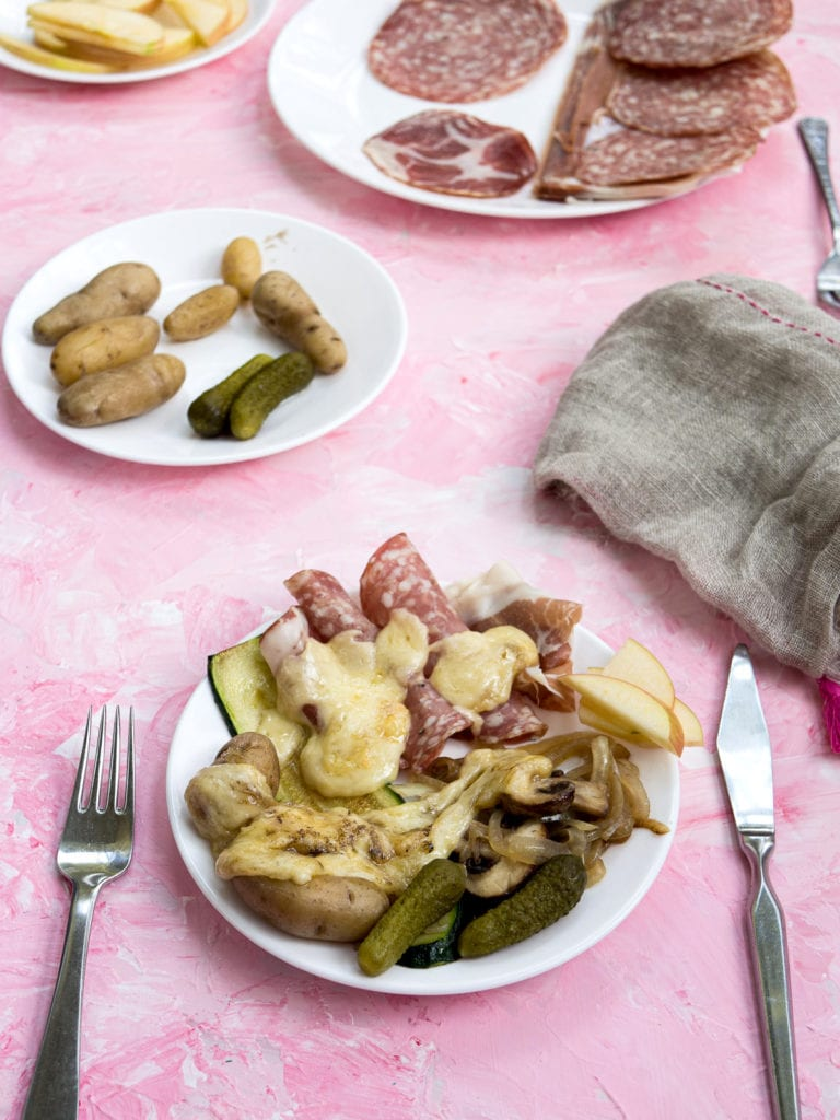 A pink table with a plate showing a raclette dinner