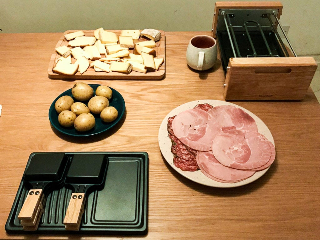 An electric tabletop raclette grill with coupelles and cheese and ham on plates