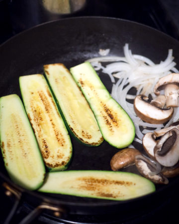 Onion, zucchini, and mushrooms cooking on a frying pan