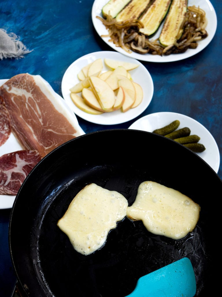 Raclette cheese frying on pan with apple slices