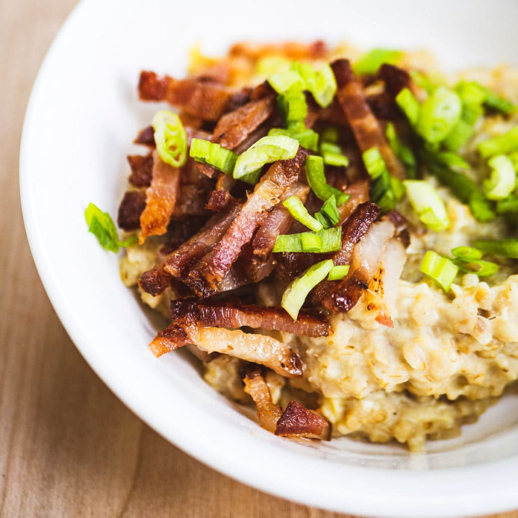 Savory oatmeal with egg topped with bacon and sliced green onions