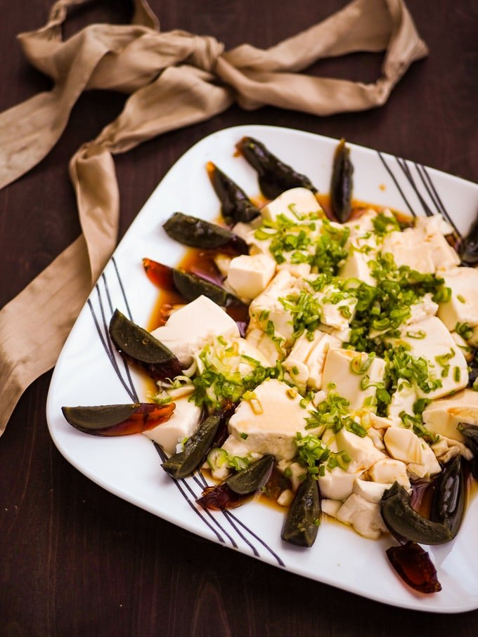 Overhead view of century egg with soft tofu, green onion, soy sauce, and sesame oil with golden ribbon in background