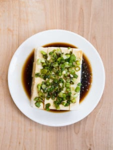 Block of silken tofu with chopped green onions and soy sauce