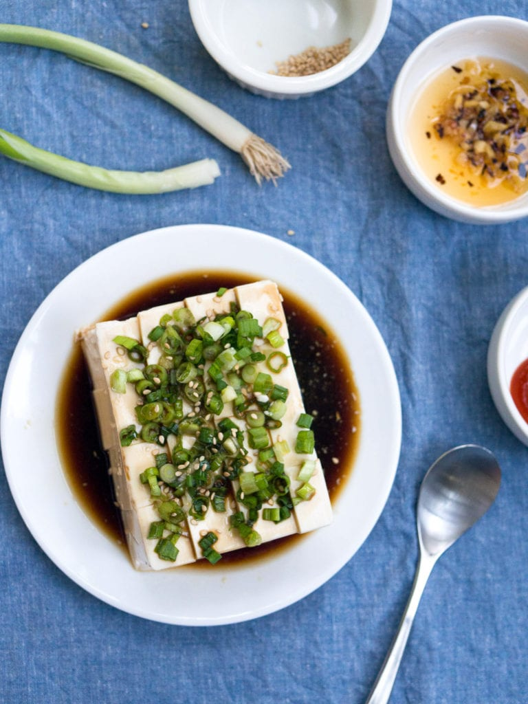 Silken Tofu Green Onion recipe on blue background with side dishes and sppon