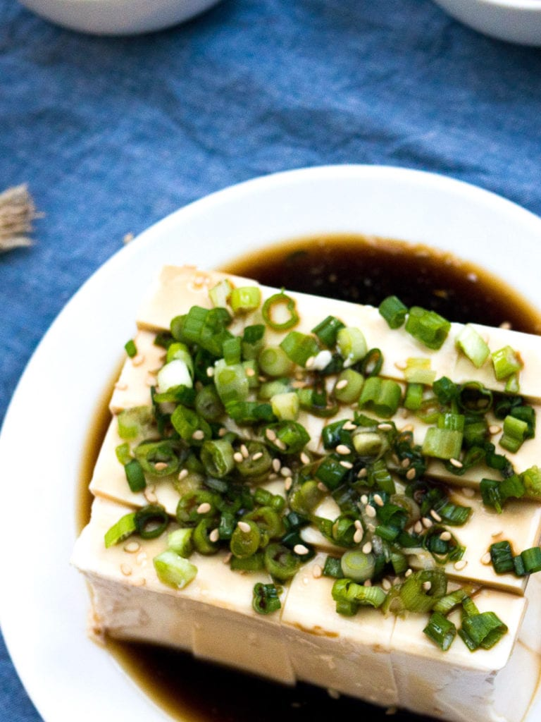 Zoomed in view of Silken Tofu with Green Onion on a white plate