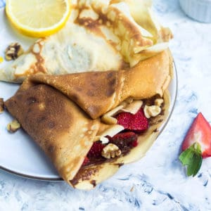 A crêpe with strawberries and nutella next to a crêpe with lemon and sugar