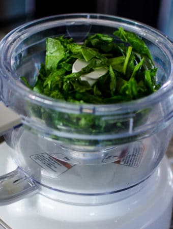 Put the spinach and basil into a food processor.