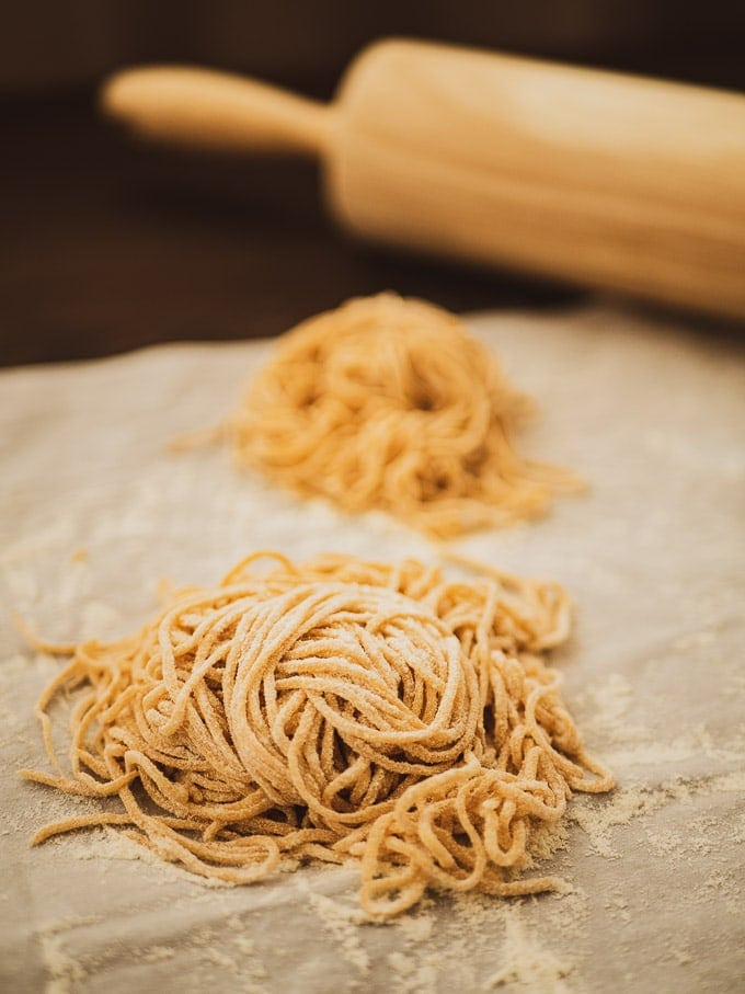 A ball of spelt pasta with a second ball and a rolling pin behind it
