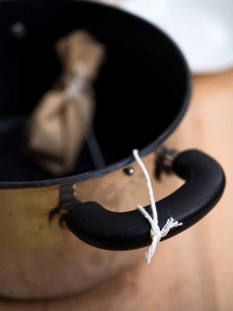 A spice sachet with the kitchen twine tied on a soup pot handle