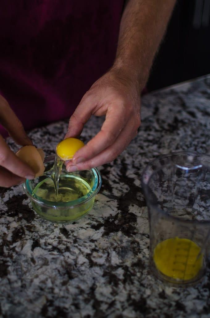 Overhead shot of separating egg whites from egg yolks. Recipe from garlicdelight.com.