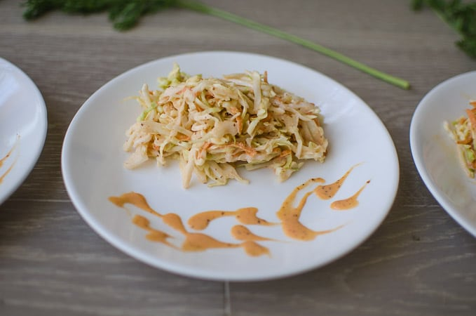 Close up shot of spicy coleslaw on white plates. Recipe from garlicdelight.com.
