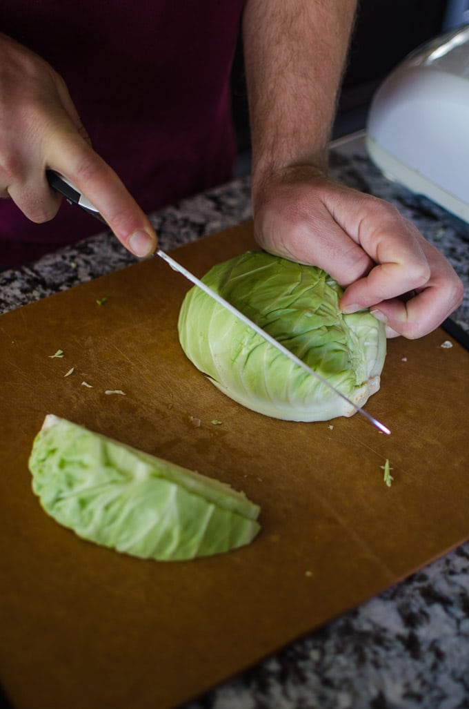 Close up shot of Alex cutting a half head of cabbage into thirds. Recipe from garlicdelight.com.