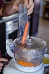 Close up shot of pushing a carrot into food processor. Recipe from garlicdelight.com.