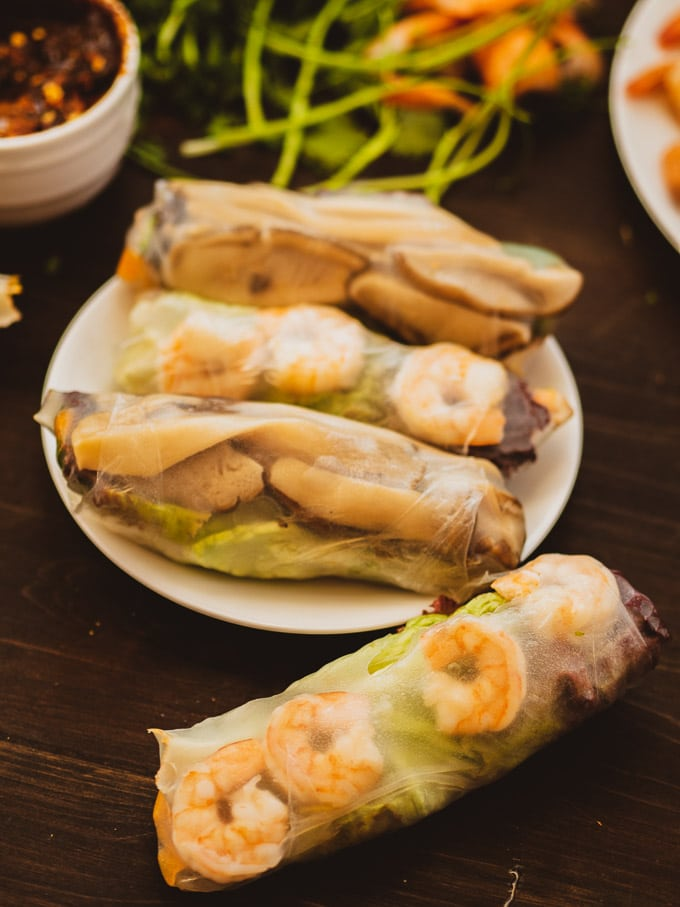 Vietnamese spring rolls with mushroom, shrimp and herbs in the background and dipping sauce on the side